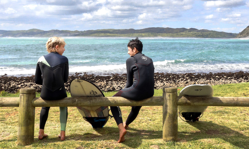 Surf culture two teeenage boys Manu beach, New Zealand