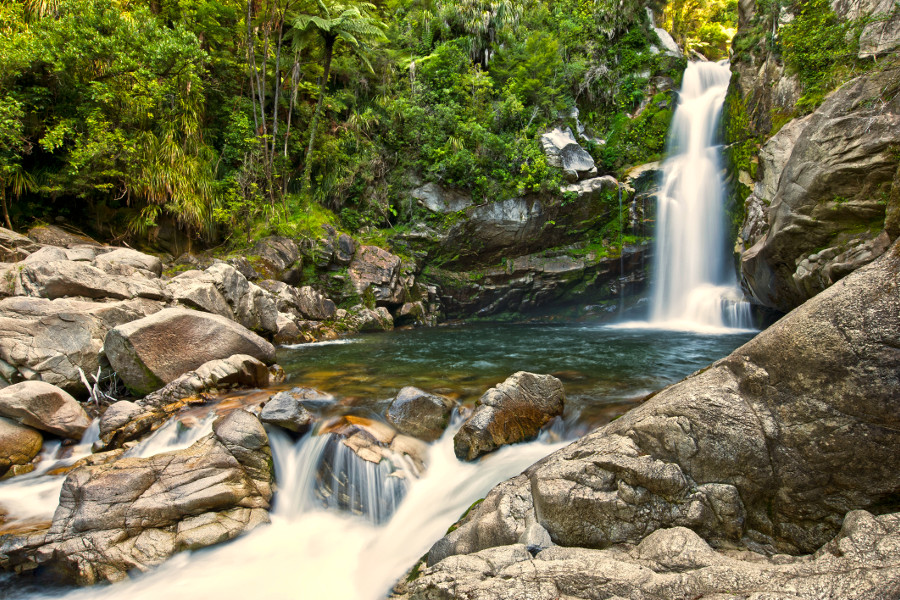 Wainui Falls, Abel Tasman National Park, South Island, New Zealand in daylight and slow shutter speed during southern hemisphere summer in February
