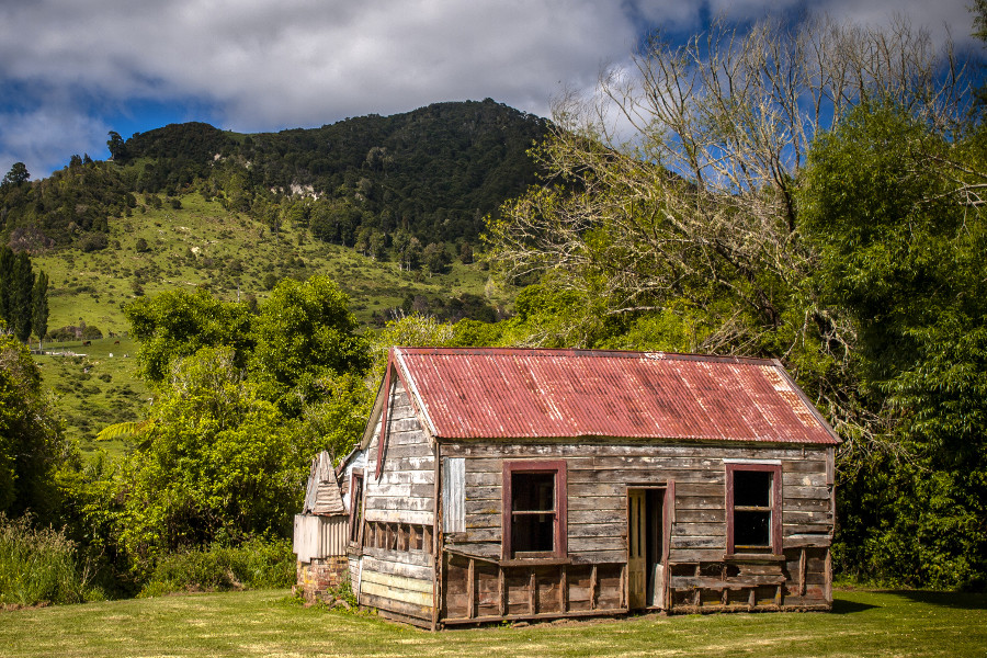 Abandoned cabin sitting in mowed field, New Zealand
