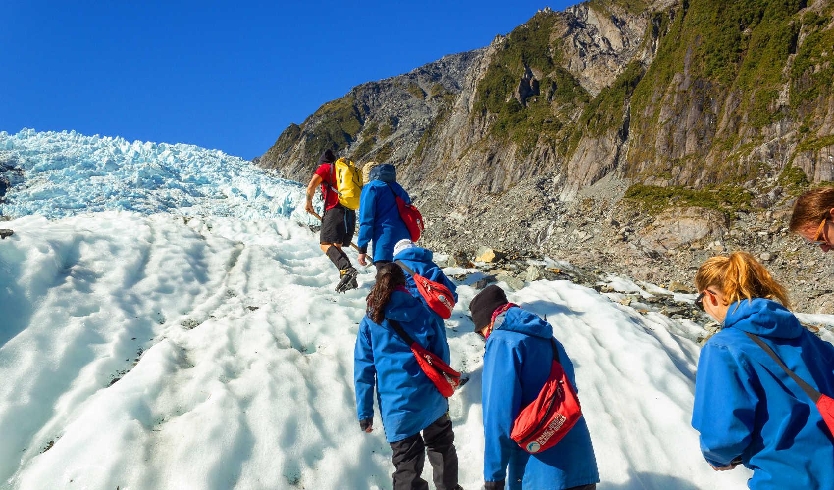 Franz Josef, New Zealand. A group of tourists hiking on Franz Josef Glacier
