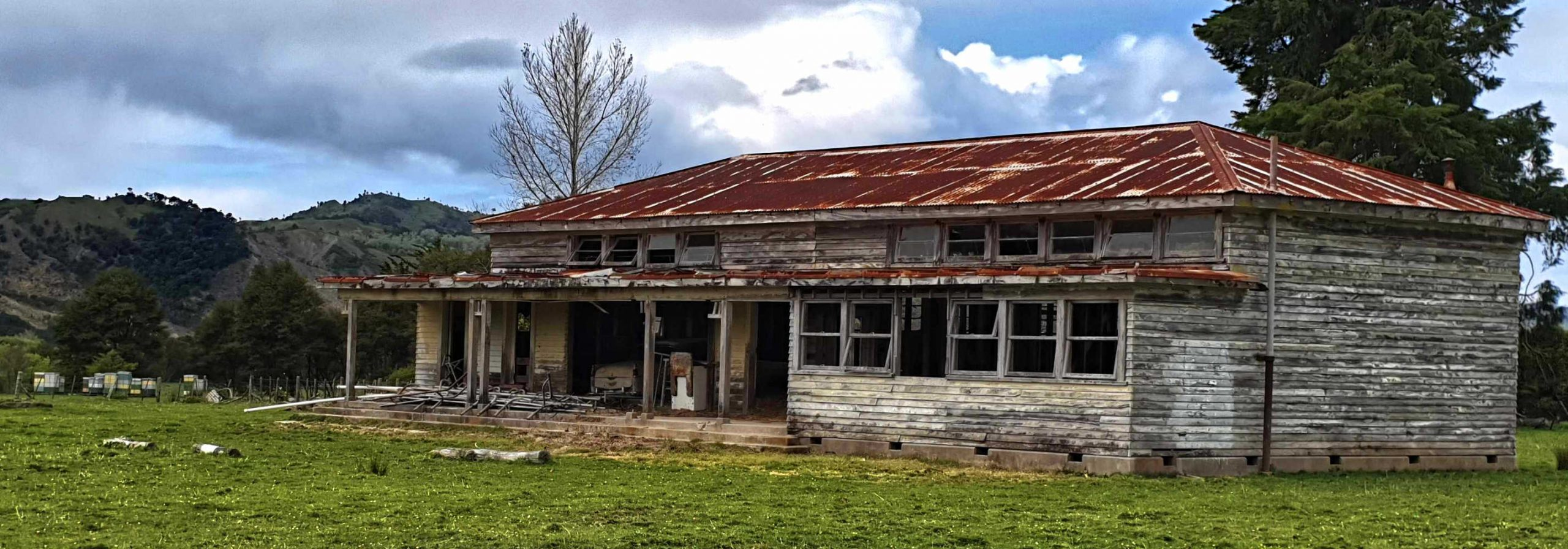 East Cape abandoned farmhouse, complete with abandoned washing machine and honey hives in nearby field,New Zealand